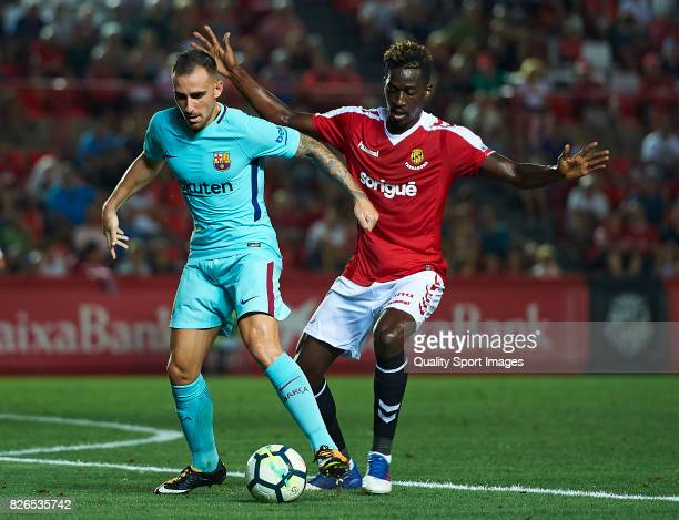 Paco Alcacer of Barcelona dispute the ball with Zahibo of Gimnastic de Tarragona during the preseason friendly match between Gimnastic de Tarragona...