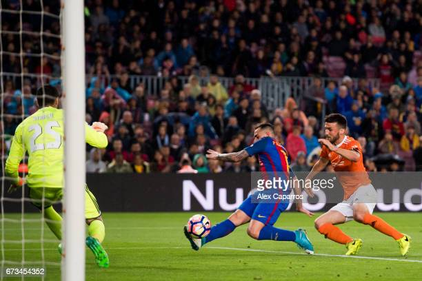 Paco Alcacer of FC Barcelona scores his team's fifth goal under pressure from Oier Sanjurjo of CA Osasuna during the La Liga match between FC...