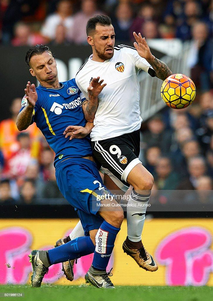 Paco Alcacer of Valencia is tackled by Alexis of Getafe during the La Liga match between Valencia CF and Getafe CF at Estadi de Mestalla on December...