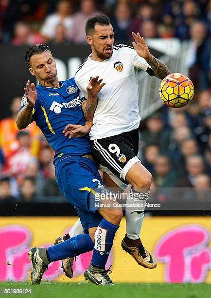 Paco Alcacer of Valencia is tackled by Alexis of Getafe during the La Liga match between Valencia CF and Getafe CF at Estadi de Mestalla on December...