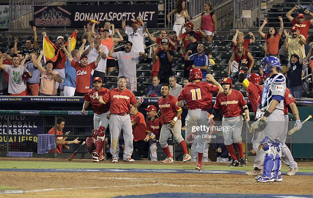 Paco Figueroa #11 of Team Spain is greeted by teammates after scoring a run in the top of the tenth inning against Team Israel during game 6 of the Qualifying Round of the World Baseball Classic at Roger Dean Stadium on September 23, 2012 in Jupiter, Florida.