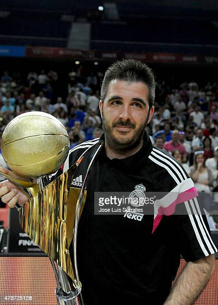 Paco Redondo Head Coach of Real Madrid poses with the trophy of champions during the Adidas Next Generation Tournament Final Game between Real Madrid...