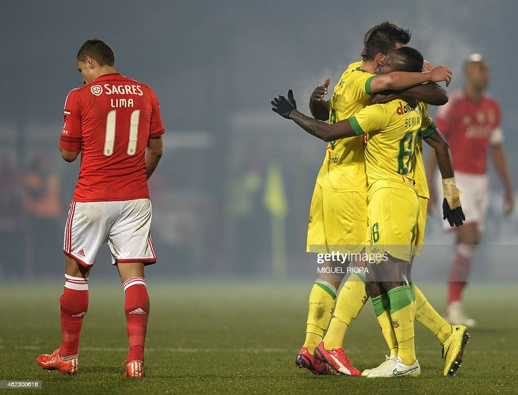 Pacos Ferreira's players celebrate their victory beside Benfica's Brazilian forward Rodrigo <a gi-track='captionPersonalityLinkClicked' href=/galleries/search?phrase=Lima+-+Brazilian+Soccer+Player&family=editorial&specificpeople=9680210 ng-click='$event.stopPropagation()'>Lima</a> (L) at the end of the Portuguese league football match FC Pacos de Ferreira vs SL Benfica at the Capital do Movel stadium in Pacos de Ferreira on January 26, 2015. Pacos won the match 1-0.