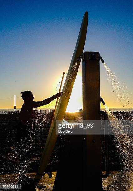 Santa Monica Ca November 26 2014 A paddle boarder and his surfboard are silhouetted by the sun as he washes down at the outdoor showers