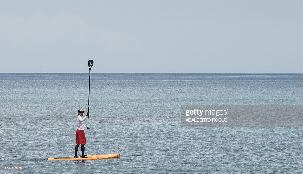 U.S. paddle boarder from Tennessee, Benjamin Schiller Friberg, raises his paddle upon departing from Marina Hemingway, on August 1, 2013 in Havana. Schiller will attempt to cross the Florida strait on his paddle board.