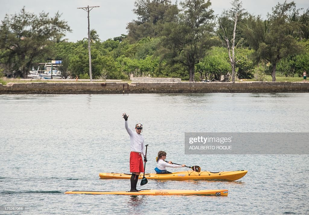 U.S. paddle boarder from Tennessee, Benjamin Schiller Friberg, waves goodbye upon departing from Marina Hemingway, on August 1, 2013 in Havana. Schiller will attempt to cross the Florida strait on his paddle board. AFP PHOTO/ADALBERTO ROQUE