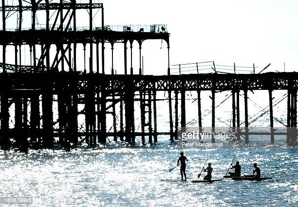 Paddle boarders make their way past the remains of the old pier in autumn sunshine near the Labour party conference on September 23 2013 in Brighton...