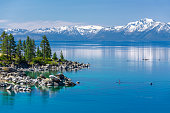 Picture of Lake Tahoe from east shore. There is a snow on the Sierra Nevada Mountains and some white clouds with reflection in turquoise waters of the lake. There is a paddle boarder arriving to the b