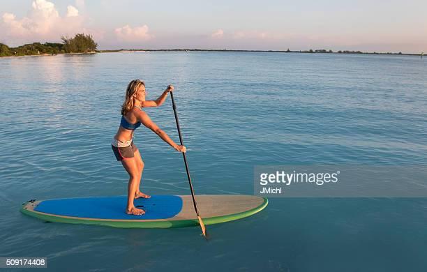 パドルボートの女性が穏やかな海湾