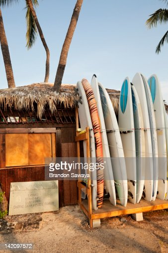 Paddle boards rest against a tropical hut in Kona.