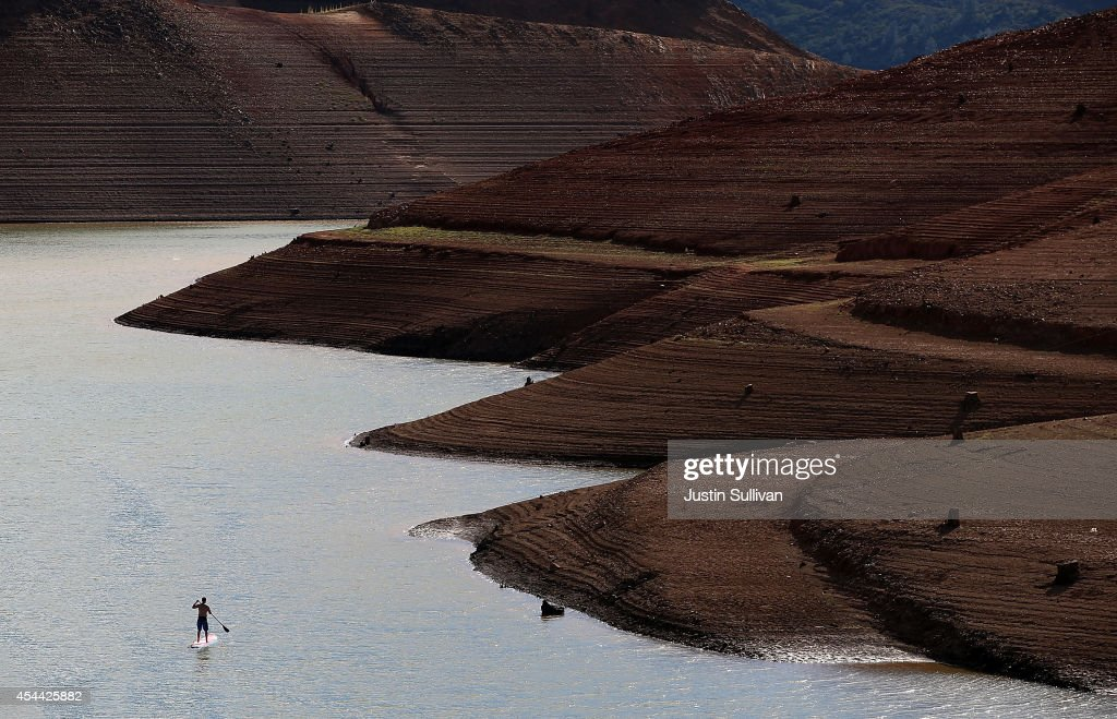 A paddleboarder floats on the waters of Shasta Lake near the Shasta Marina Resort on August 30 2014 in Lakehead California As the severe drought in...