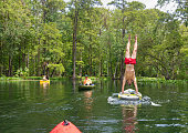 A young man does a hand stand on a paddleboard on the Silver River in the Ocala National Forest.