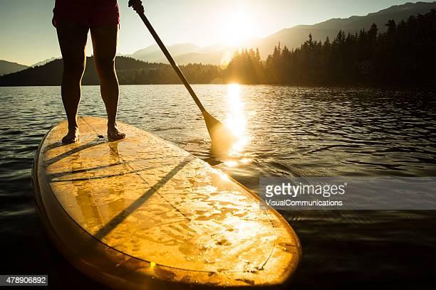 Paddleboard sur le lac au lever du soleil ou au soleil couchant.