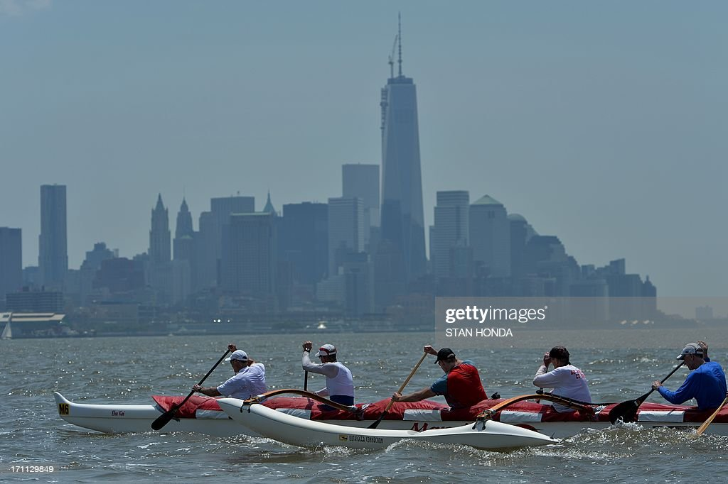 Paddlers from the Manu'iwa Canoe Club in an outrigger canoe pass Lower Manhattan and One World Trade Center (C) during the Hawaiian Airlines Liberty Challenge race June 22, 2013 in New York harbor. The traditional water sport in Polynesian culture is in its 17th year of competition in New York. AFP PHOTO/Stan HONDA