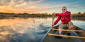 senior paddler enjoying paddling a canoe on a calm lake at sunset, Riverbend Ponds Natural Area, Fort Collins, Colorado