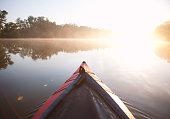 Paddling kayak on foggy river in morning sunrise light