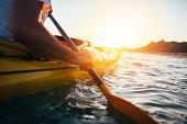 Close up of man holding kayak paddle at sunset. Copy space.