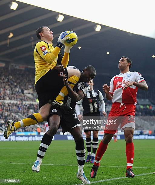 Paddy Kenny of Queens Park Rangers claims the ball from Shola Ameobi of Newcastle United during the Barclays Premier League match between Newcastle...