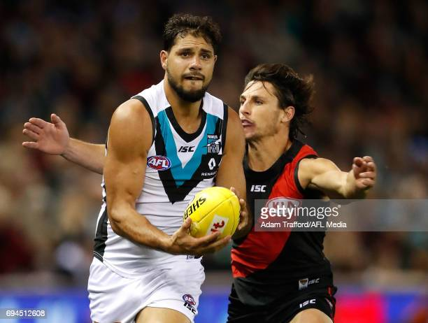 Paddy Ryder of the Power is tackled by Mark Baguley of the Bombers during the 2017 AFL round 12 match between the Essendon Bombers and the Port...