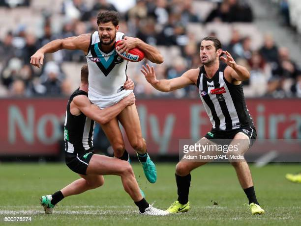 Paddy Ryder of the Power is tackled by Taylor Adams of the Magpies while Brodie Grundy of the Magpies looks on during the 2017 AFL round 14 match...