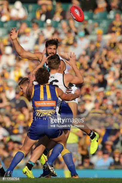 Paddy Ryder of the Power taps the ball to Ollie Wines of the Power during the round 16 AFL match between the West Coast Eagles and the Port Adelaide...