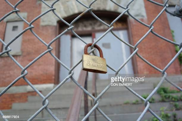 A padlock is clipped to the fence of a closed public schoolhouse on May 30 2017 in Newburgh New York Rows of boardedup homes became a ubiquitous...