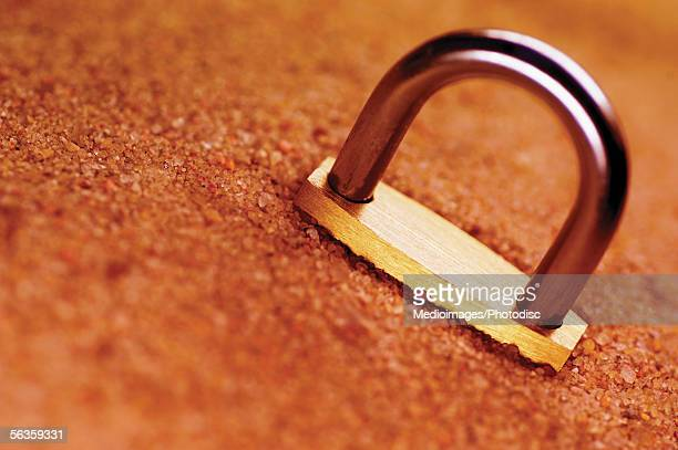 Padlock partially buried in sand