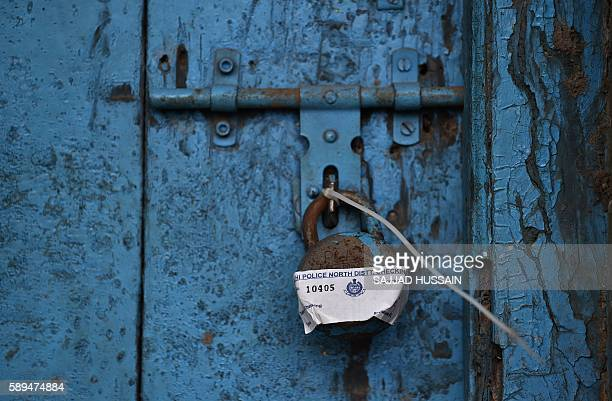 TOPSHOT A padlock sealed by a member of the Indian Delhi Home Guard hangs from the door of a shop near the Red Fort area in New Delhi on August 14...