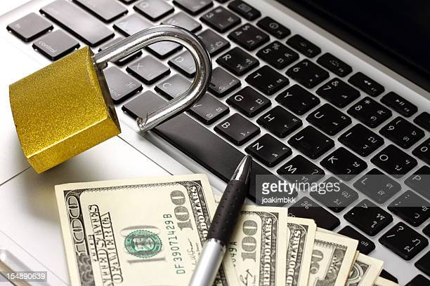 Padlock with US dollars on a laptop computer