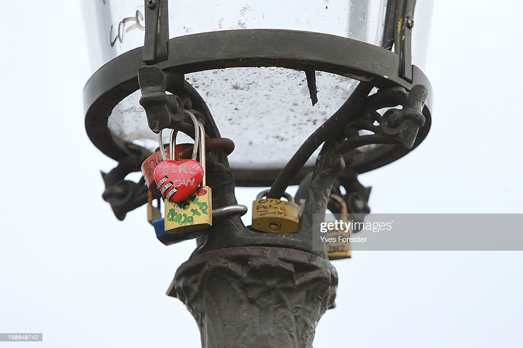 Padlocks adorn the lamp on the Pont des Arts on January 4, 2013 in Paris, France. The nine-arch metallic footbridge completed in 1804 is one of the most romantic places of the capital where people visit it to attach love padlocks illustrated with their initials or messages of love, before throwing the key into the River Seine. The bridge is also a meeting place for artists who find inspiration from the surrounding views of the city.