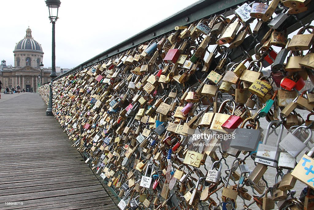 Padlocks adorn the Pont des Arts on January 4, 2013 in Paris, France. The nine-arch metallic footbridge completed in 1804 is one of the most romantic places of the capital where people visit it to attach love padlocks illustrated with their initials or messages of love, before throwing the key into the River Seine. The bridge is also a meeting place for artists who find inspiration from the surrounding views of the city.