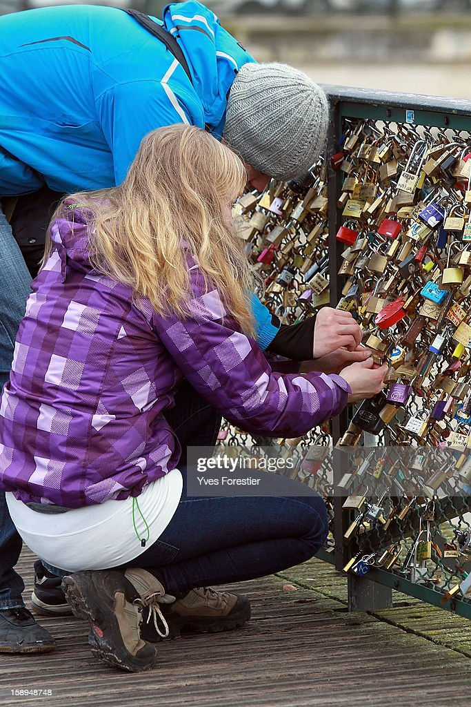 Padlocks are attached to the Pont des Arts on January 4, 2013 in Paris, France. The nine-arch metallic footbridge completed in 1804 is one of the most romantic places of the capital where people visit it to attach love padlocks illustrated with their initials or messages of love, before throwing the key into the River Seine. The bridge is also a meeting place for artists who find inspiration from the surrounding views of the city.