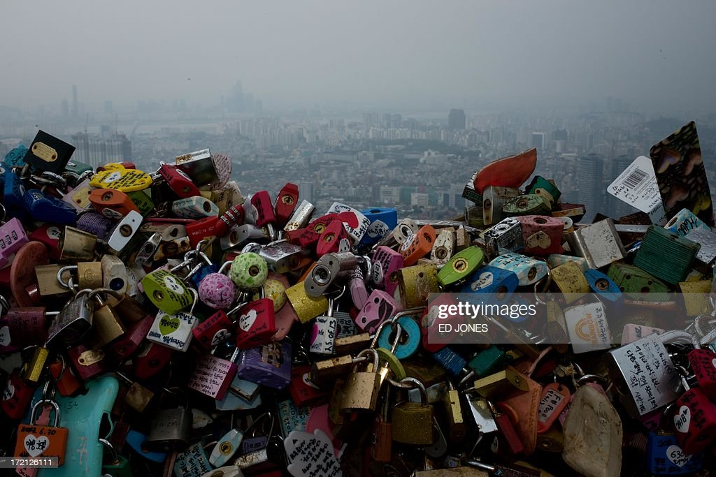Padlocks inscribed with messages hang off a fence before the Seoul city skyline during heavy rain on July 2, 2013. July marks the wet season for Seoul during which the city of10 million people receives some 60 percent of its annual rainfall. AFP PHOTO / Ed Jones