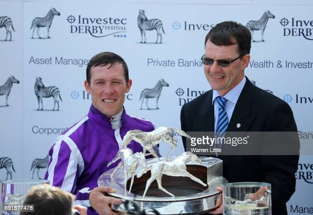 Padraig Beggy riding Wings Of Eagles celebrates victory with the trophy alongside trainer Aidan O'Brien after the Investec Derby at Epsom Racecourse...