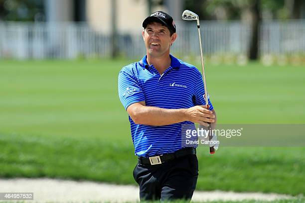 Padraig Harrington of Ireland plays his shot out of a fairway bunker on the 18th hole during the continuation of the fourth round of The Honda...