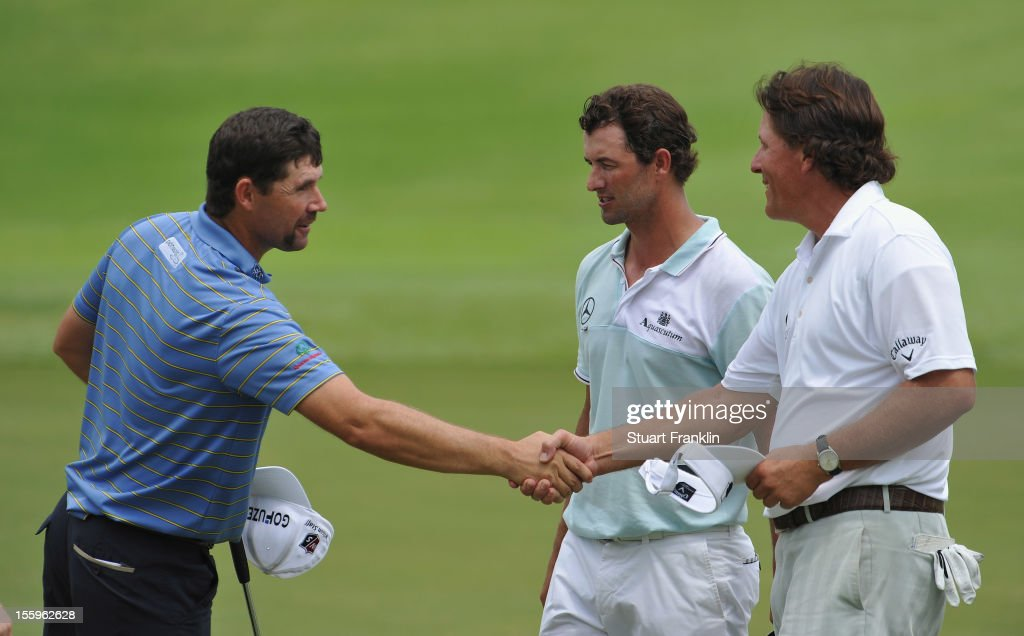 Padraig Harrington of Ireland shakes hands with Phil Mickelson of USA and Adam Scott of Australia during the resumption of the rain delayed second round of the Barclays Singapore Open at the Sentosa Golf Club on November 10, 2012 in Singapore.