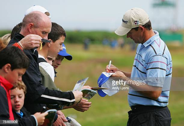 Padraig Harrington of Ireland signs autographs for fans during a practice round during previews to The 136th Open Championship at the Carnoustie Golf...