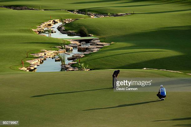 Padraig Harrington of Ireland watches his playing partner Camilo Villegas of Colombia hole out at the 18th hole during the third round of the Dubai...