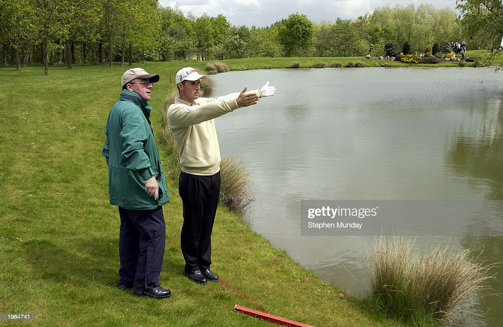 Padraig Harrington of Ireland with Referee John Grant deciding the correct position for his penalty drop after driving in to the water on the par...