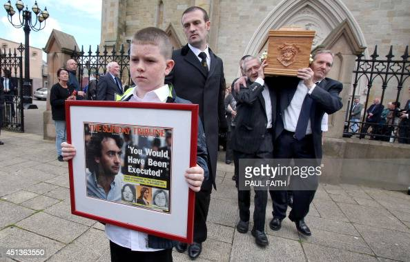 Padraig McKernan aged 10 great nephew of Gerry Conlon carries a framed newspaper headline in front of the coffin of Gerry Conlon as it is carried...