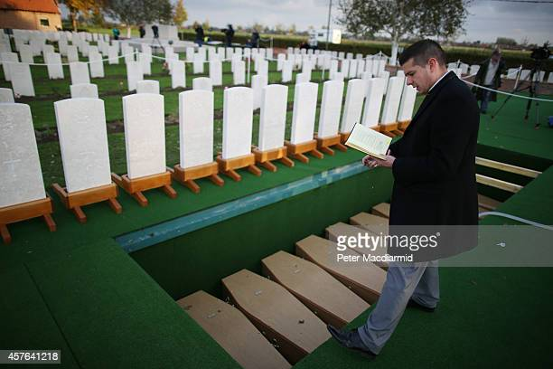 A padre blesses the coffins containing the remains of 15 British World War One soldiers at the Commonwealth War Graves Commission YFarm Cemetery on...