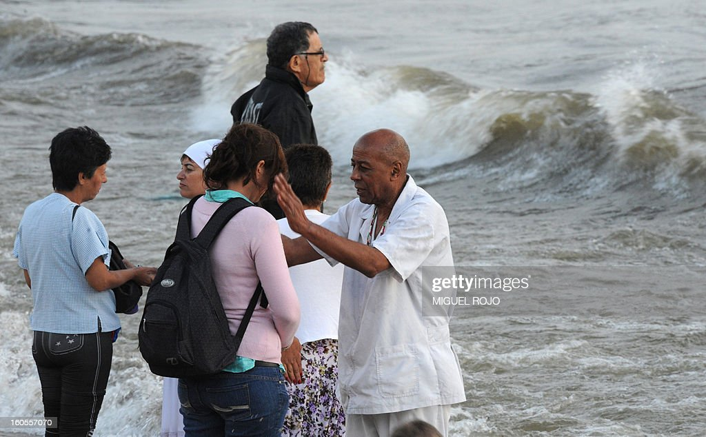 A 'Pae' -priest of the Afro-American Umbandista cult- cleanses a sympathizer, during the celebration of Iemanja -the African goddess of the sea- in Montevideo on February 2, 2013. Thousands of faithful and onlookers gather throughout the country's coast for this celebration. AFP PHOTO/Miguel ROJO