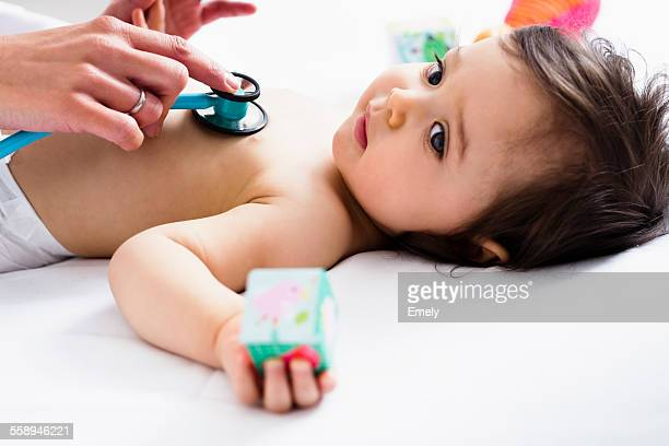 Paediatrician checking baby boys heart using stethoscope