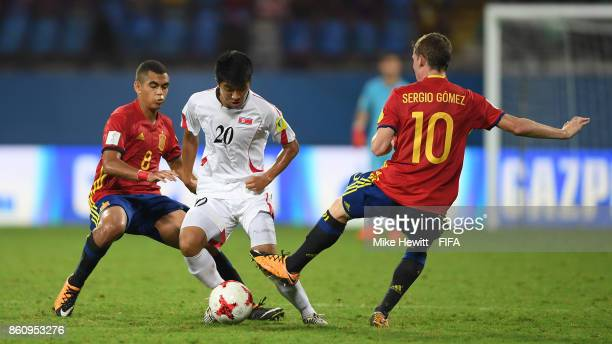 Paek Kwang Min of Korea DPR is challenged by Mohamed Moukhliss and Sergio Gomez of Spain before receiving a red card during the FIFA U17 World Cup...