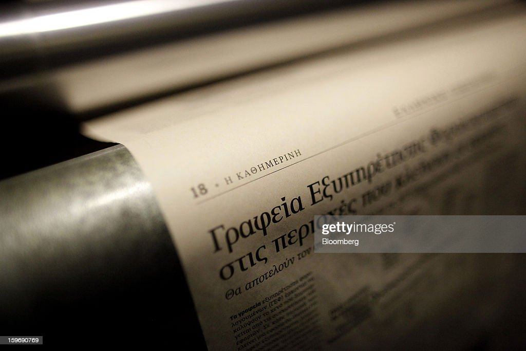 A page of the Kathimerini newspaper passes through the print presses at the Kathimerini printing plant in Paiania, Greece, on Thursday, Jan. 17, 2013. An anarchist group claimed responsibility for a series of attacks early on Jan. 11 when unidentified perpetrators threw makeshift bombs made from propane gas canisters into the homes of five Greek journalists working for national media saying it was to protest coverage of the country's financial crisis seen as sympathetic to the government. Photographer: Kostas Tsironis/Bloomberg via Getty Images