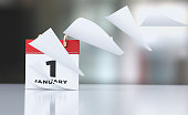 Pages of a red calendar standing over defocused background are flying away. January 1st writes on the calendar. Horizontal composition with copy space. Calendar and reminder concept with selective foc