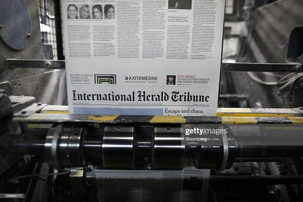 Pages of the International Herald Tribune newpaper run through the print presses at the Kathimerini printing plant in Paiania, Greece, on Thursday, Jan. 17, 2013. An anarchist group claimed responsibility for a series of attacks early on Jan. 11 when unidentified perpetrators threw makeshift bombs made from propane gas canisters into the homes of five Greek journalists working for national media saying it was to protest coverage of the country's financial crisis seen as sympathetic to the government. Photographer: Kostas Tsironis/Bloomberg via Getty Images