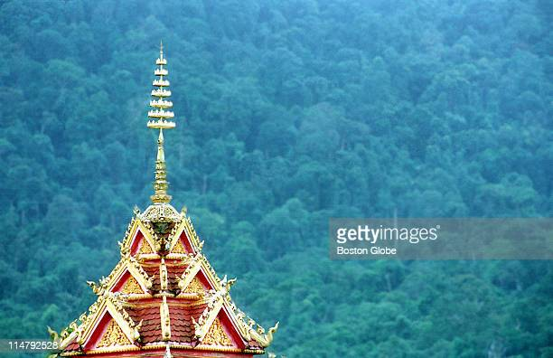 A pagoda spire cuts a sharp contrast against a background of jungle foliage in the outskirts of Pakse in Laos