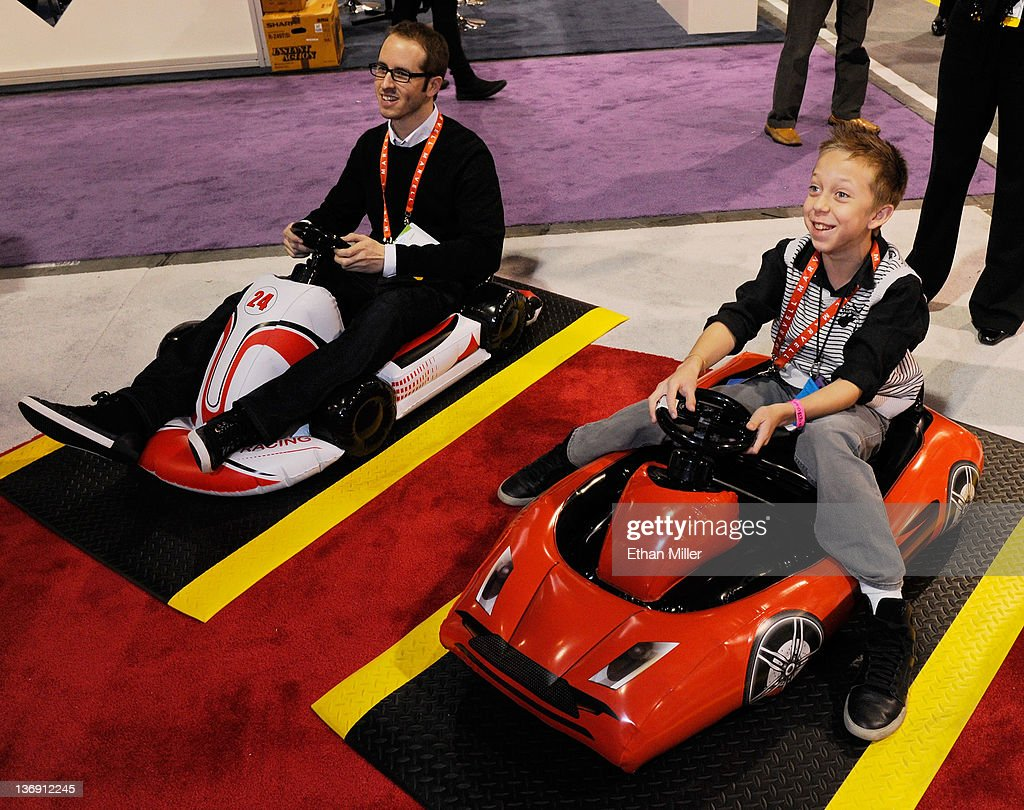 Paid models Camilo Gallardo (L) and Christopher Jacobs demonstrate Inflatable Sports Cars for the Nintendo Wii at the CTA Digital booth at the 2012 International Consumer Electronics Show at the Las Vegas Convention Center January 12, 2012 in Las Vegas, Nevada. CES, the world's largest annual consumer technology trade show, runs through January 13 and features more than 3,100 exhibitors showing off their latest products and services to about 140,000 attendees.