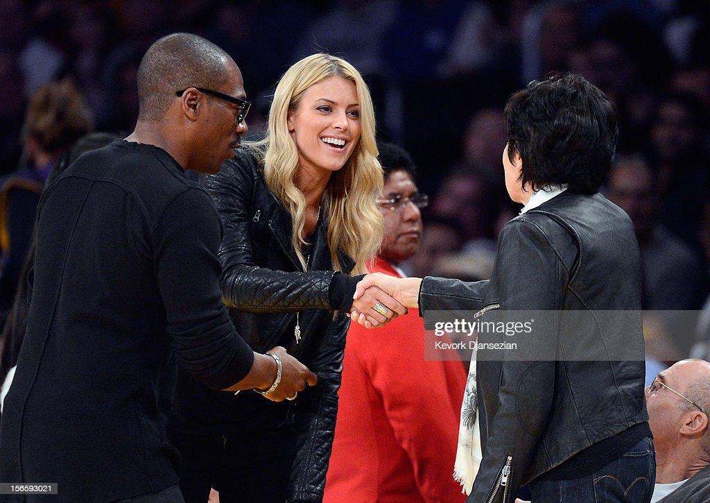 Paige Butcher, (C) 33-year old Australian model, and girlfriend of actor Eddie Murphy, greets Marilyn Katzenberg, wife of Jeffrey Katzenberg, CEO of DreamWorks Animation, as they attends the NBA basketball game between Los Angeles Lakers and Phoenix Suns at Staples Center with Murphy on November 16, 2012 in Los Angeles, California.